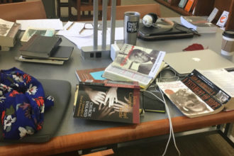 In the library, table covered with books