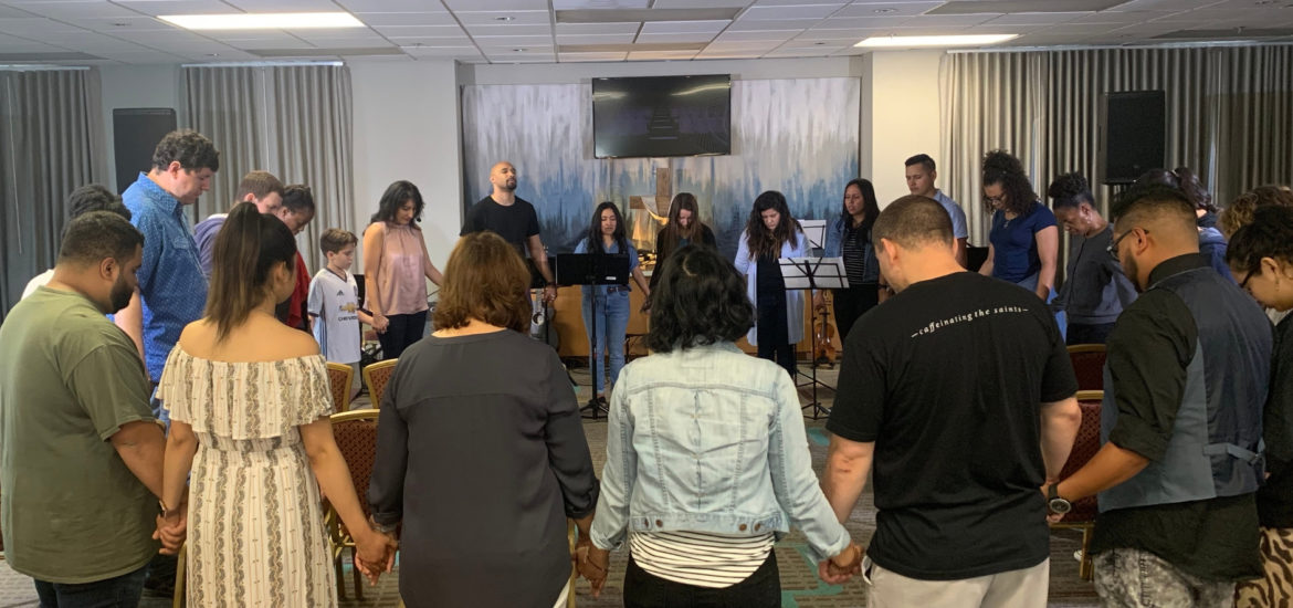 Own Your Faith - May 2019 - Ines praying with leaders at Own Your Faith